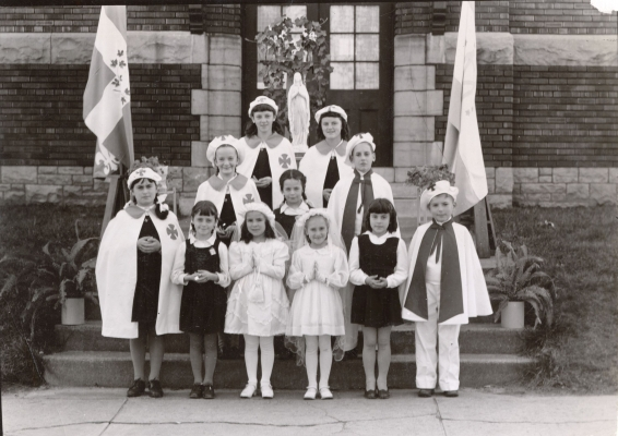Black and white photograph showing a group of children of various ages standing in front of, or on, a staircase leading to the front door of a brick building. Some are dressed in school uniforms, others in communion dresses or special costumes with matching cape and hat.