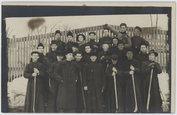 Black and white photograph, taken in winter, of a group of some fifteen young men accompanied by a few adults. The group is arranged in three rows, posing in front of a wooden fence. The younger members of the group wear cassocks and hold hockey sticks. The adults, wearing long winter coats and fur hats, appear among the hockey players, at the front of the group, in the centre, and at the sides.