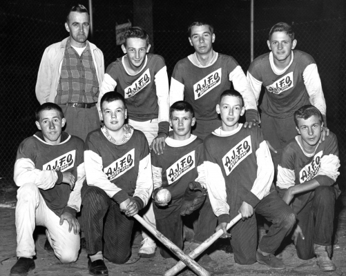 "Black and white photograph of a group of eight teens accompanied by a middle-aged man. Five young men are kneeling, with the other three standing behind them. All boys wear ""A.J.F.O. Notre-Dame"" jerseys, and three in the front hold baseball equipment."