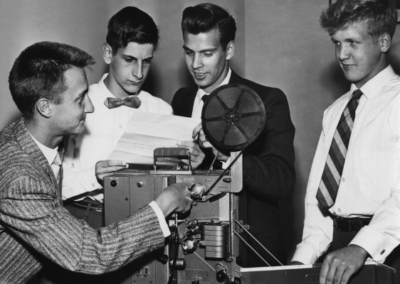 Black and white photograph of four male teens around a projector. The two young men in the center of the image are reading a document, and a third is operating the projector. They are all well-dressed.