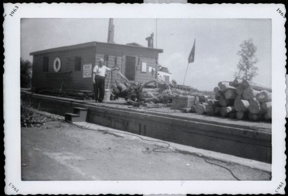 Black and white photograph of an elderly man standing on a moored barge. The barge is loaded with logs.