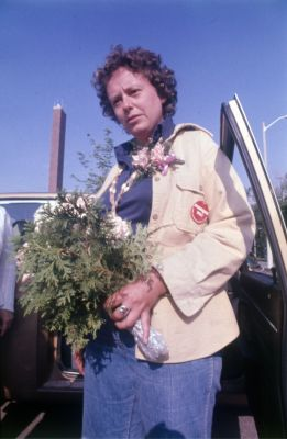 Colour photograph of a young woman in casual dress, wearing a corsage and a red button on her jacket. She is getting out of a car, a bouquet in her hands.