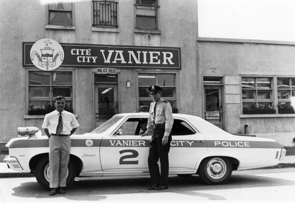 Black and white photograph showing a smiling man and a serious-looking policeman by a police car in the town of Vanier. The car is parked in front of a Vanier building.
