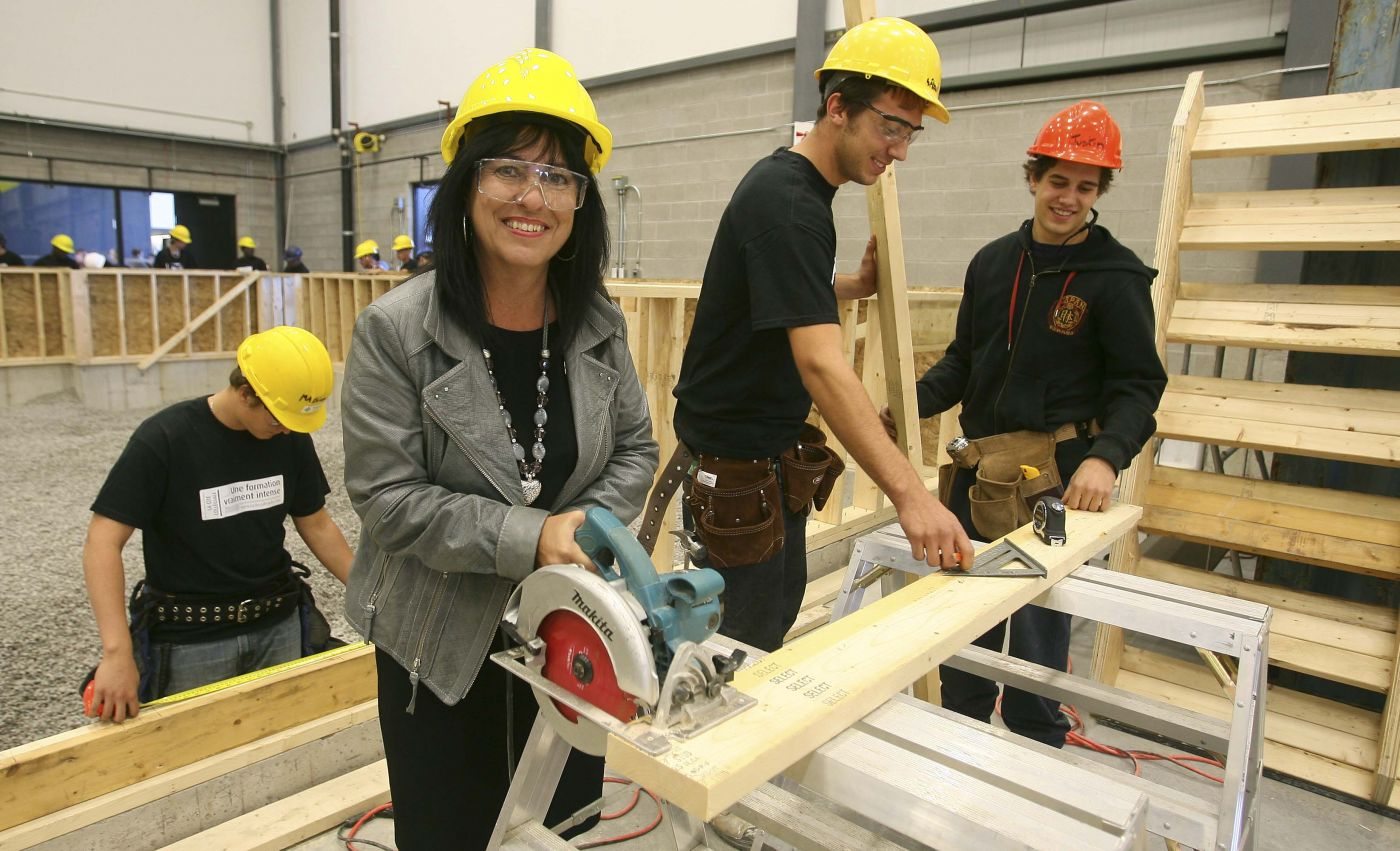 Colour photograph showing three young men and a middle-aged woman in a carpentry workshop, holding different tools. They are wearing hard hats, some also wearing protective glasses, and working around a wooden board. More workers are visible in the background.