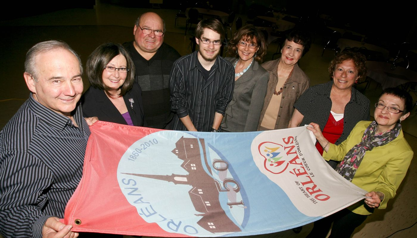 Colour photograph of a group of people, including two older man, two older women, three middle-aged women, and a young man. The group is gathered around a colourful banner commemorating the 150th anniversary of Orléans.