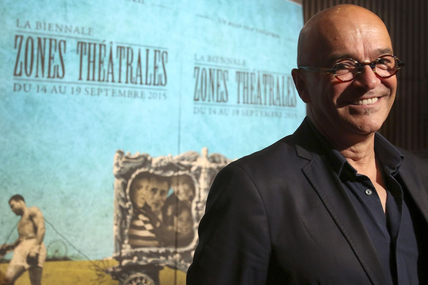 "Colour photograph of a bald, smiling, middle-aged man. He wears glasses and a dark suit, standing in front of pale blue posters bearing the words ""LA BIENNALE ZONES THÉÂTRALES DU 14 AU 19 SEPTEMBRE 2015"""