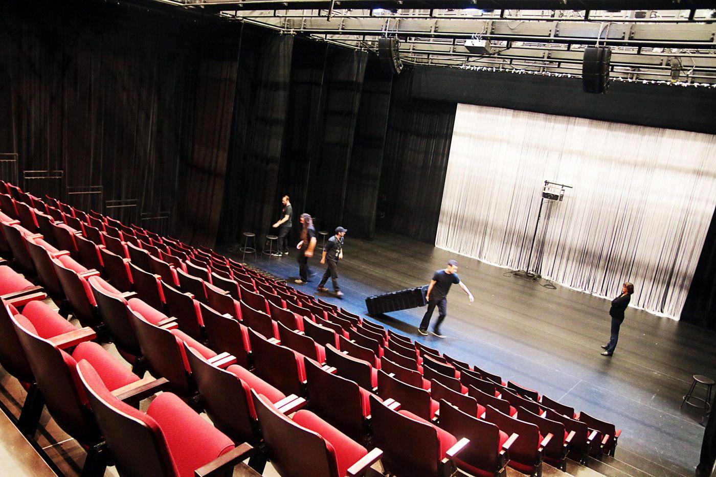 Photographie en couleur, prise de biais. Une salle de théâtre vue d'en haut, à partir des rangées de sièges rouge vif disposées en gradins. Cinq techniciens vêtus en noir travaillent sur la scène.