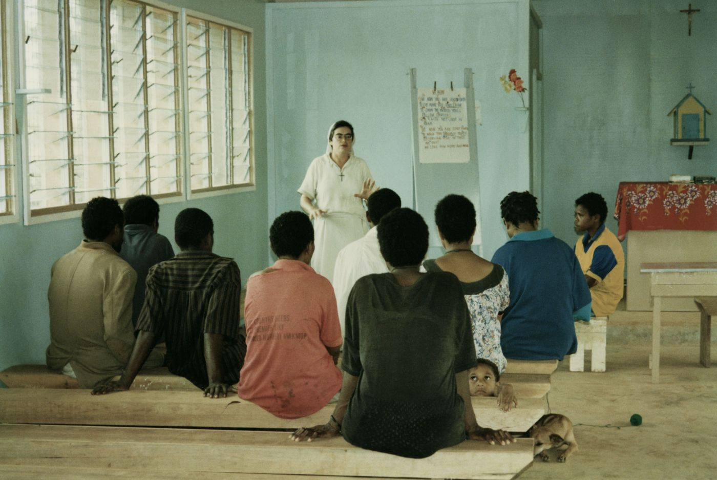 Colour photograph of a middle-aged nun, dressed in white. She is teaching a group of nine black adults in a rudimentary classroom. The students are sitting on wooden benches. A young boy and a dog are also present in the classroom.