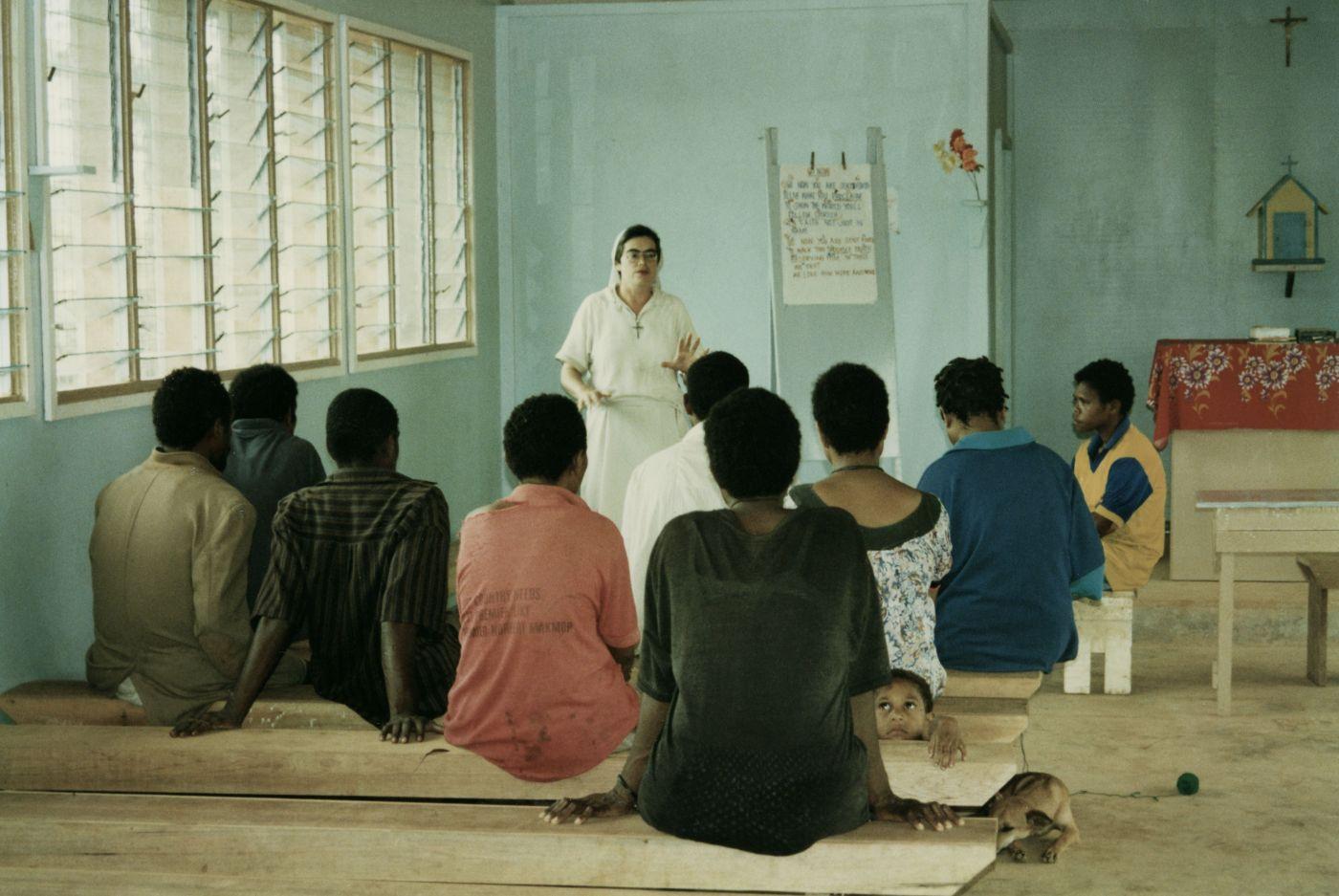 Photographie en couleur d'une religieuse d'âge moyen, vêtue de blanc. Elle enseigne à un groupe de neuf adultes noirs dans une salle de classe rudimentaire. Les étudiants sont assis sur des bancs de bois. Un jeune garçon et un chien sont aussi dans la salle de classe.