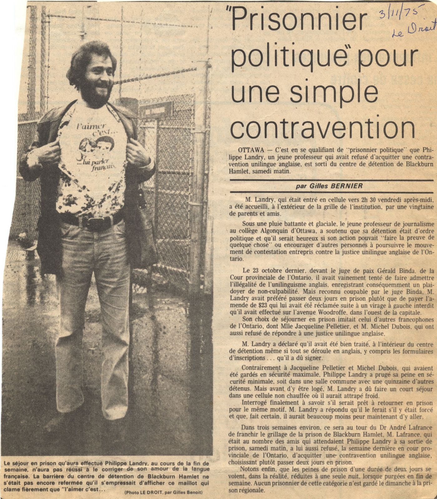 "Newspaper article written in French, with the source and date handwritten in blue ink. The article is accompanied by a black and white photograph of a young bearded man revealing a T-shirt with the words ""L'aimer c'est… lui parler français"" (Love is ... speaking to them in French). In the background, a chain link fence."