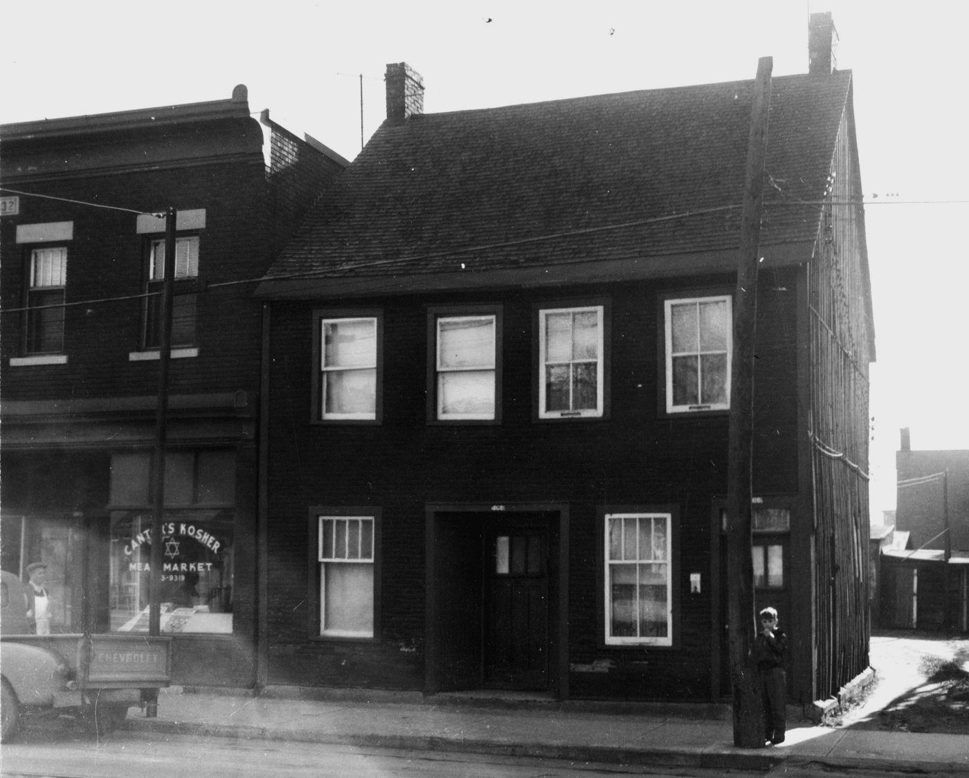 Photographie en noir et blanc d'un jeune garçon devant une maison en bois à deux étages. Un camion et un homme sont devant le commerce Cantor's Kosher Meat Market.
