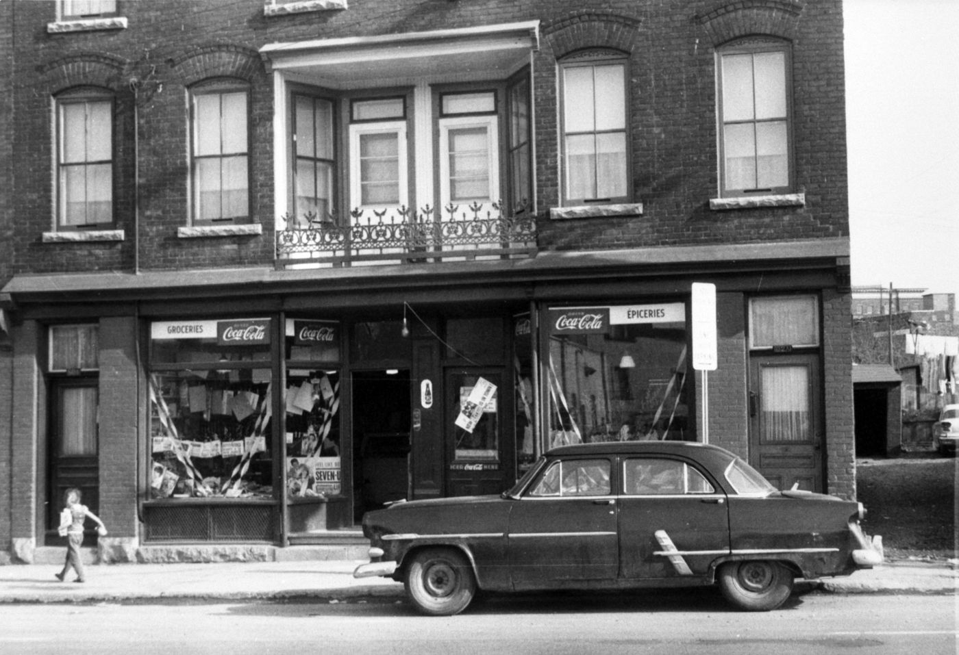 Black and white photograph of a young boy walking in front of a multi-storey brick house, with a grocery store on the ground floor. The signs are bilingual. A car is parked in front of the shop.