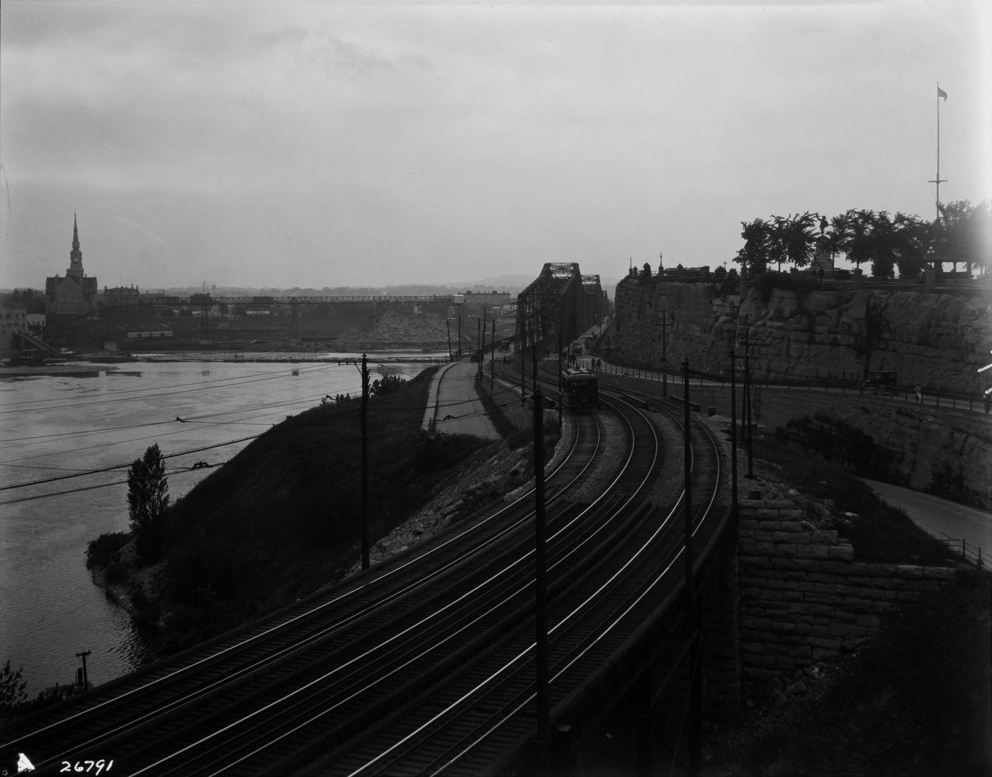 Black and white photograph of a riverside landscape. In the foreground, three railways lead to an iron bridge. On the other side of the river, an industrial landscape dominated by an imposing church.
