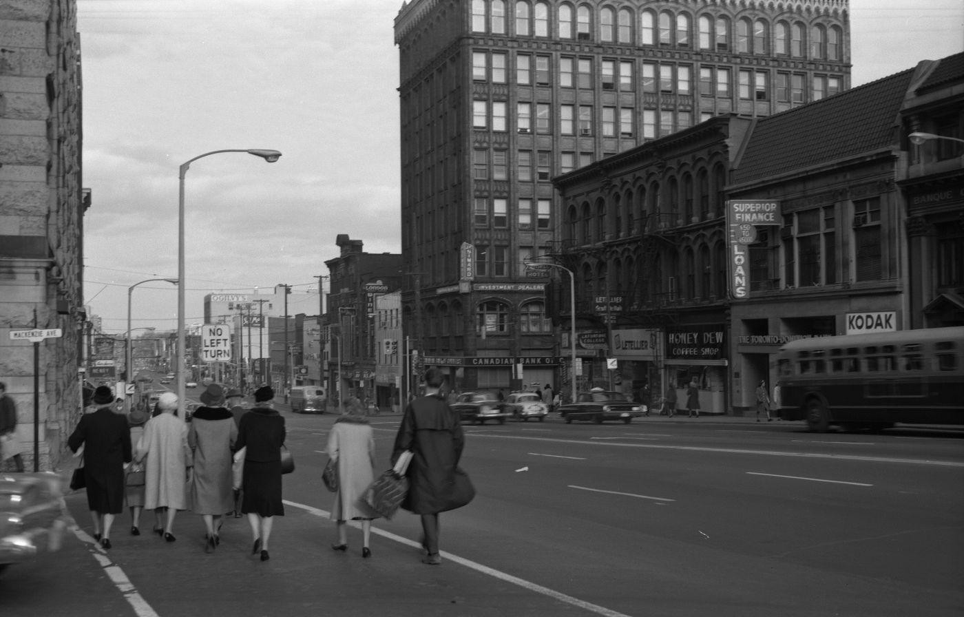 Photographie en noir et blanc d'une rue passante avec édifices de plusieurs étages et panneaux publicitaires. À l'avant-plan, un groupe de piétons bien mis traverse une rue transversale.
