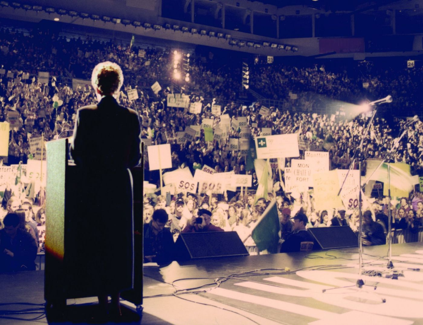 """Colour photograph of a woman seen from behind, standing on a stage, addressing the audience from a podium with a microphone. The stadium is filled with people brandishing signs bearing the slogan """"S.O.S. Montfort."""""""