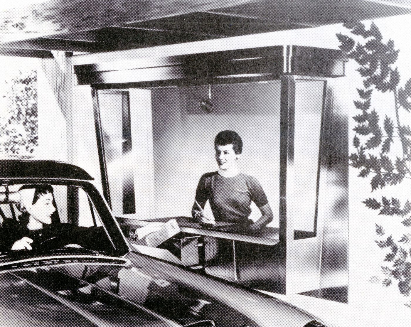 Black and white photograph of an elegant young woman sitting in her car, handing money through the window to a smiling, modern-looking young woman working at a drive-through service counter.