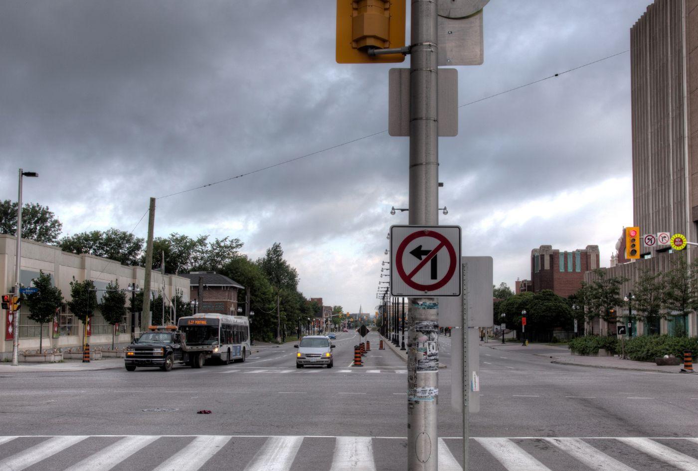 Photographie en couleur d'un boulevard à six voies. On peut y voirdes voitures, un autobus et des panneaux routiers. Un édifice à plusieurs étages et d'autres immeubles récents font aussi partie du paysage.