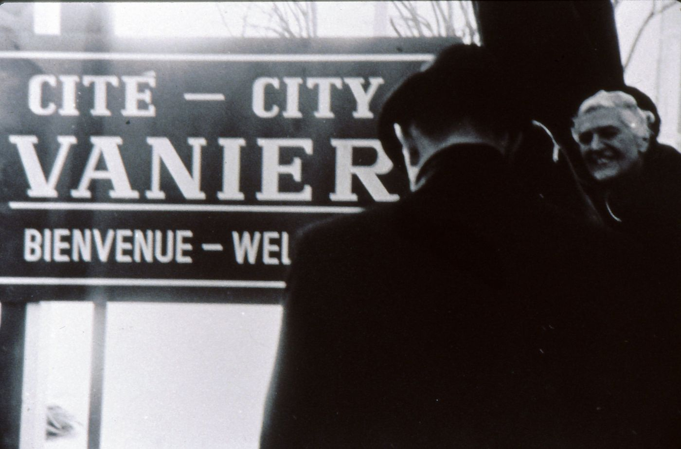 Black and white photograph showing a smiling mature woman and a man, from behind. Both are dressed with black coats and wear hats. They stand in front of a bilingual Vanier welcome sign.