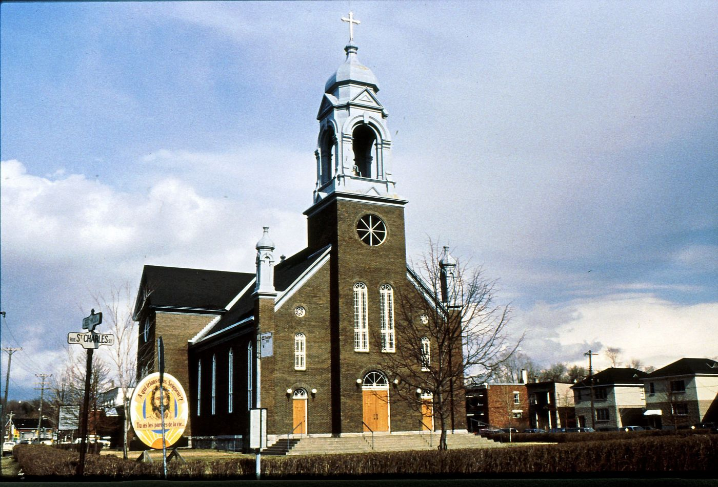 Colour photograph of a dark brown brick church with a striking silver bell tower surmounted by a cross. The facade of the church has three doors, four long windows, and a large bull's-eye window. The church is located near a busy street, in a residential area.
