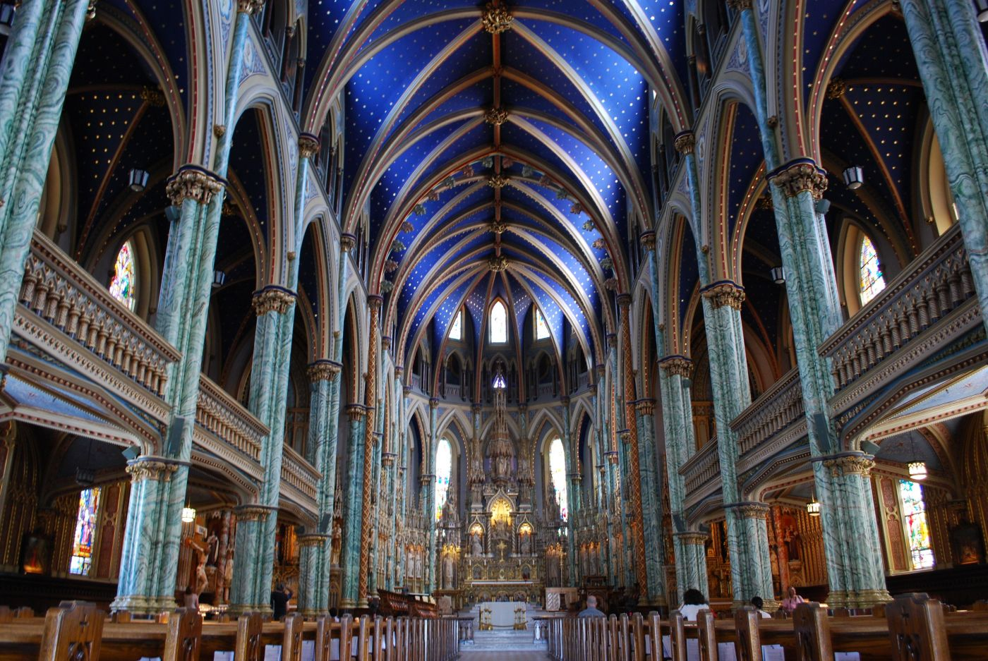 Colour photograph of the interior of a neo-Gothic-style church. Columns of green and white marble line the nave on each side. The vaulted ceiling is painted blue. The sanctuary is richly carved.