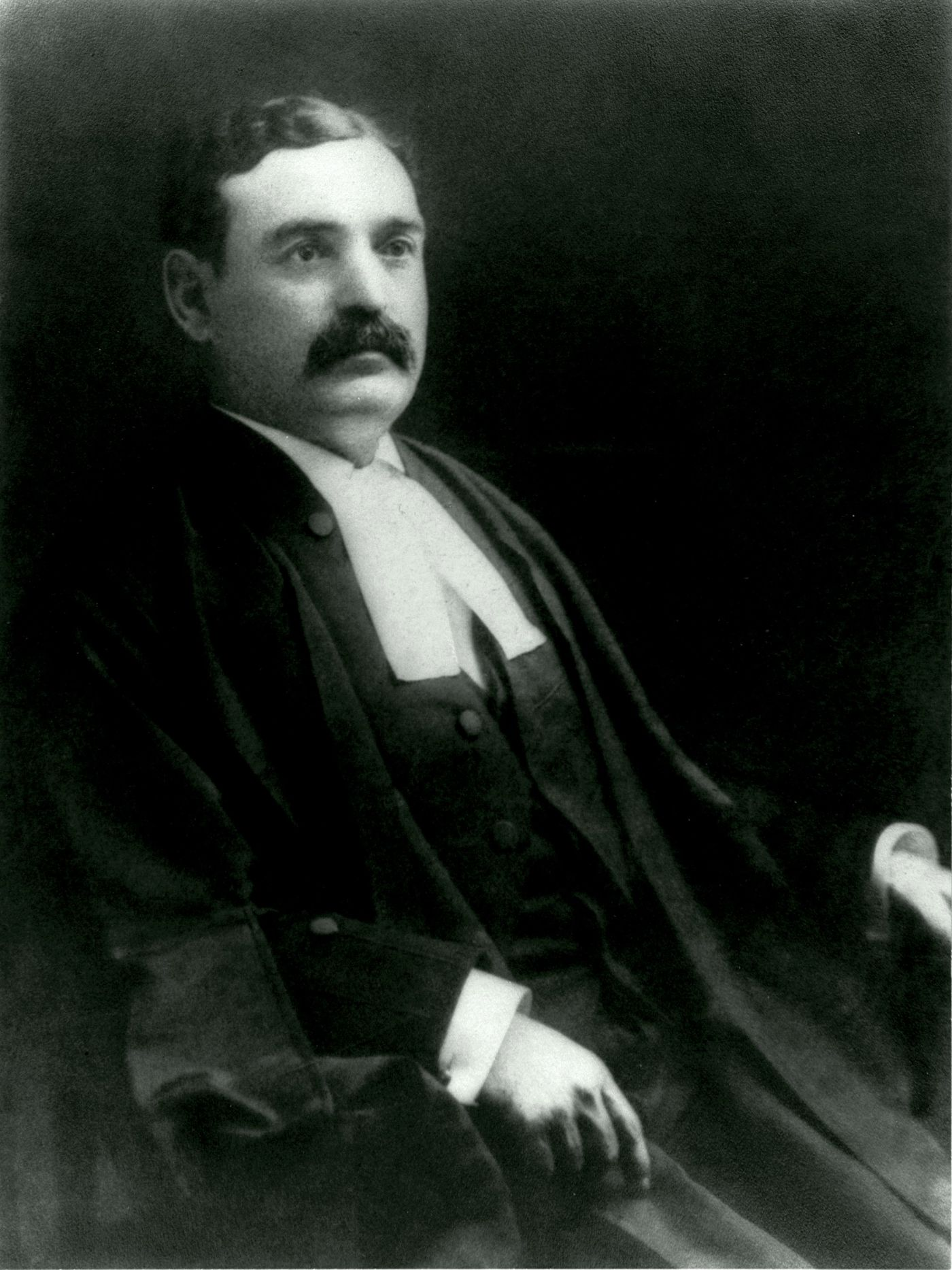 Black and white studio photograph of a middle-aged man sporting a mustache. He wears the long, loose gown and white collar of a lawyer.