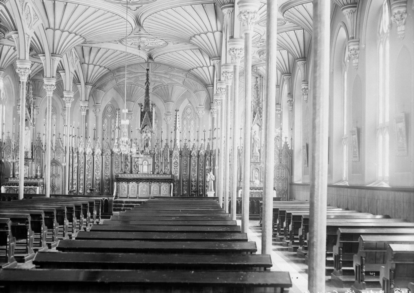 Photographie en noir et blanc de l'intérieur d'une petite église, où s'alignent de nombreux bancs. Son plafond à voûtes en éventail en bois sculpté est soutenu par de fines colonnes. L'autel est très orné.