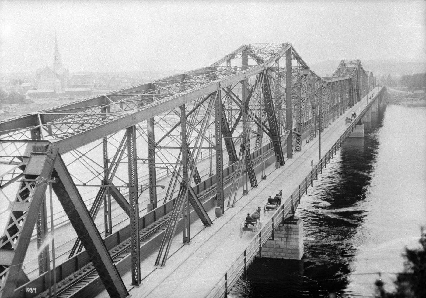 Black and white photograph of a steel trellis bridge overlooking a river. Viewed from one end of the bridge, horse-drawn buggies head towards the opposite bank where there is a church.