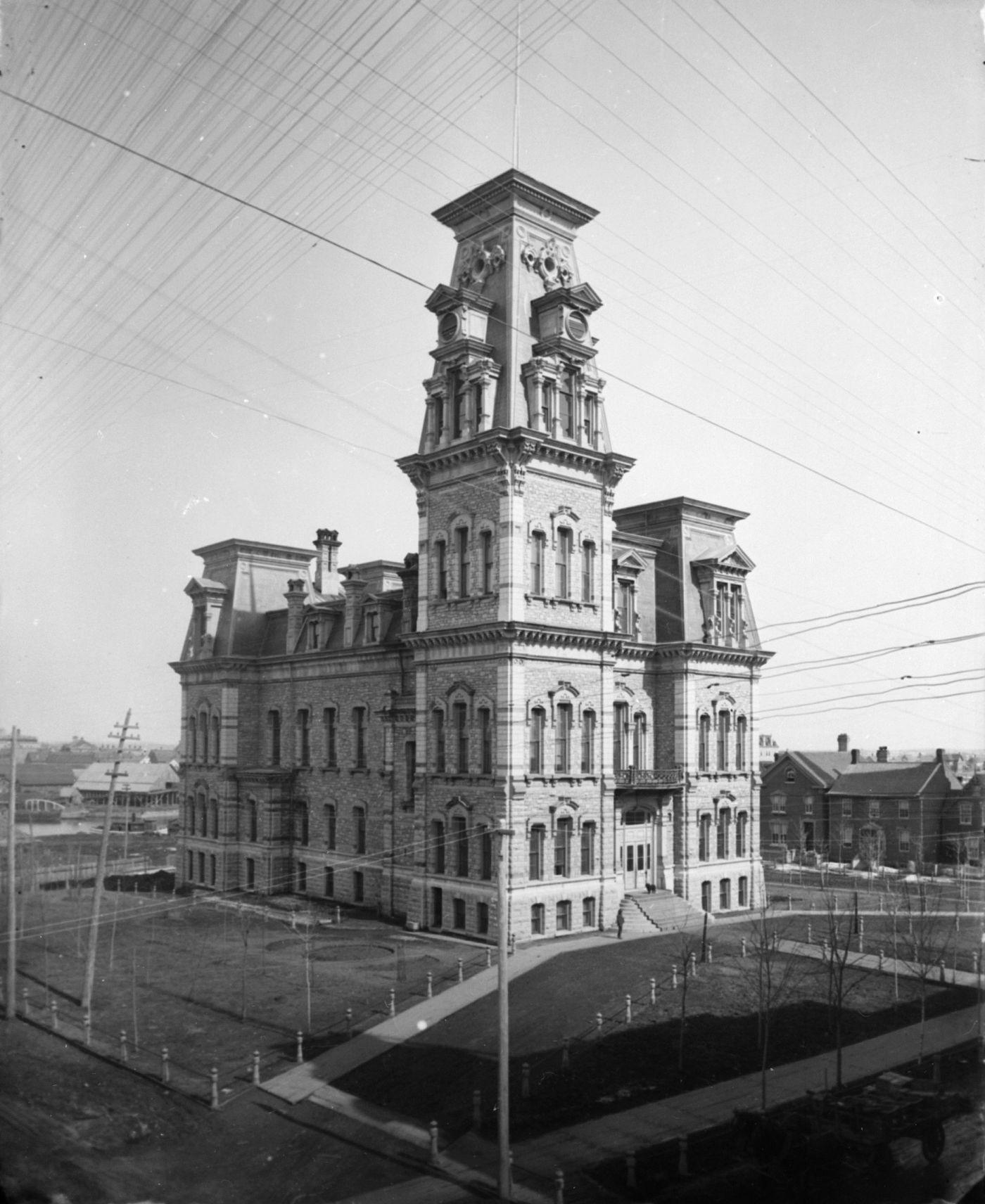 Photographie en noir et blanc d'un édifice en pierre à quatre étages, dominé par une tour à sa droite. L'édifice est séparé des maisons avoisinantes par un parc. Des lignes diagonales sont visibles en haut de l'image.