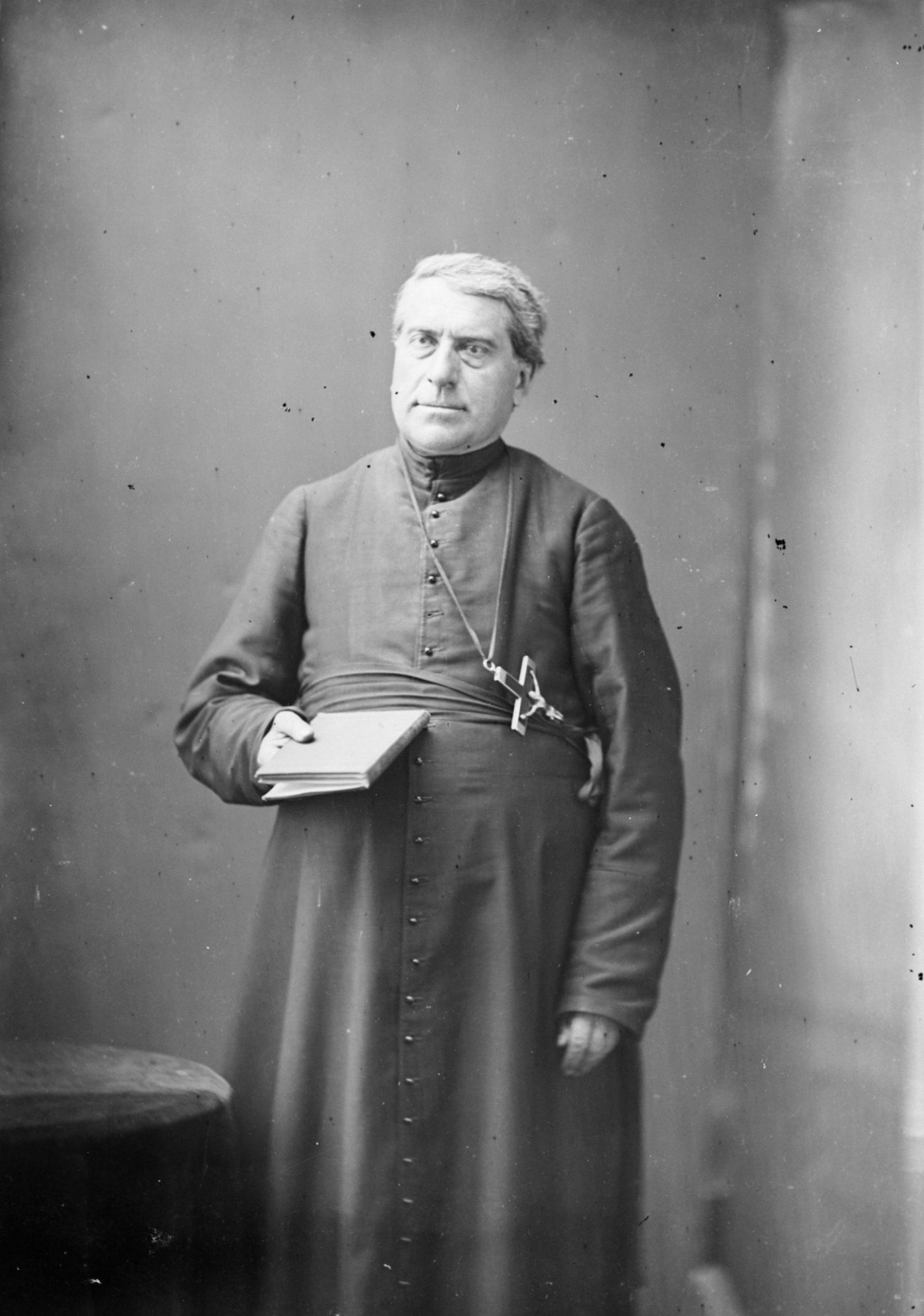 Black and white studio photograph of a mature priest wearing a cassock and a large cross. He is standing, holding a book in his right hand.