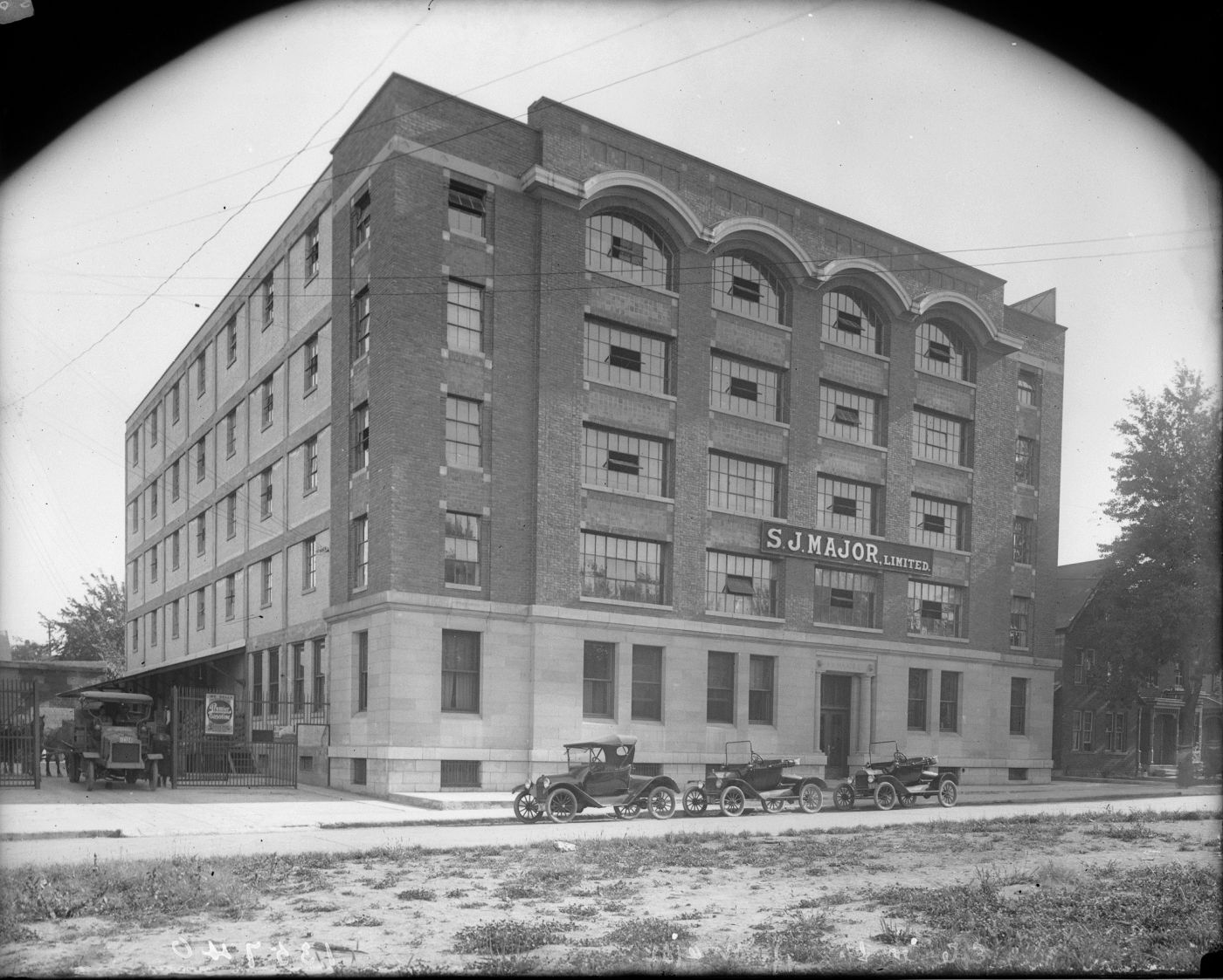 Black and white photograph of a six-storey brick building adorned with large windows. A sign bears the name of the business. Three vintage cars are parked in front of the main entrance.
