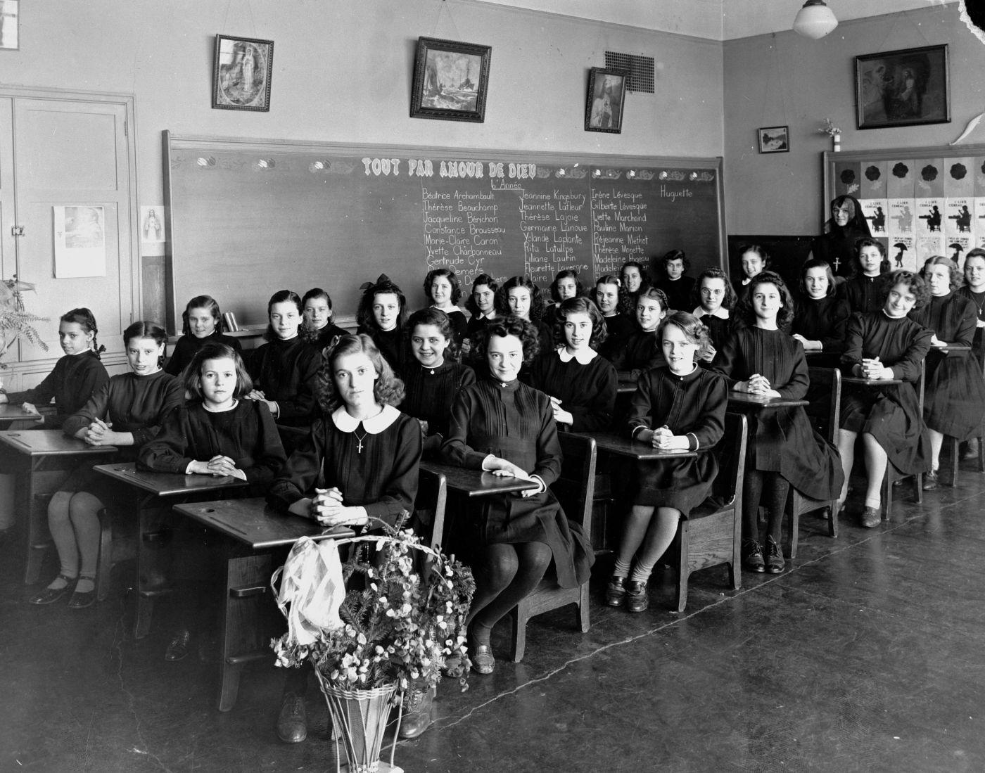 Photographie en noir et blanc d'une salle de classe vue en angle. Une trentaine de jeunes filles en robes noires sont assises à des pupitres. La classe compte sept rangées de quatre pupitres. Une religieuse est debout au fond de la salle de classe.
