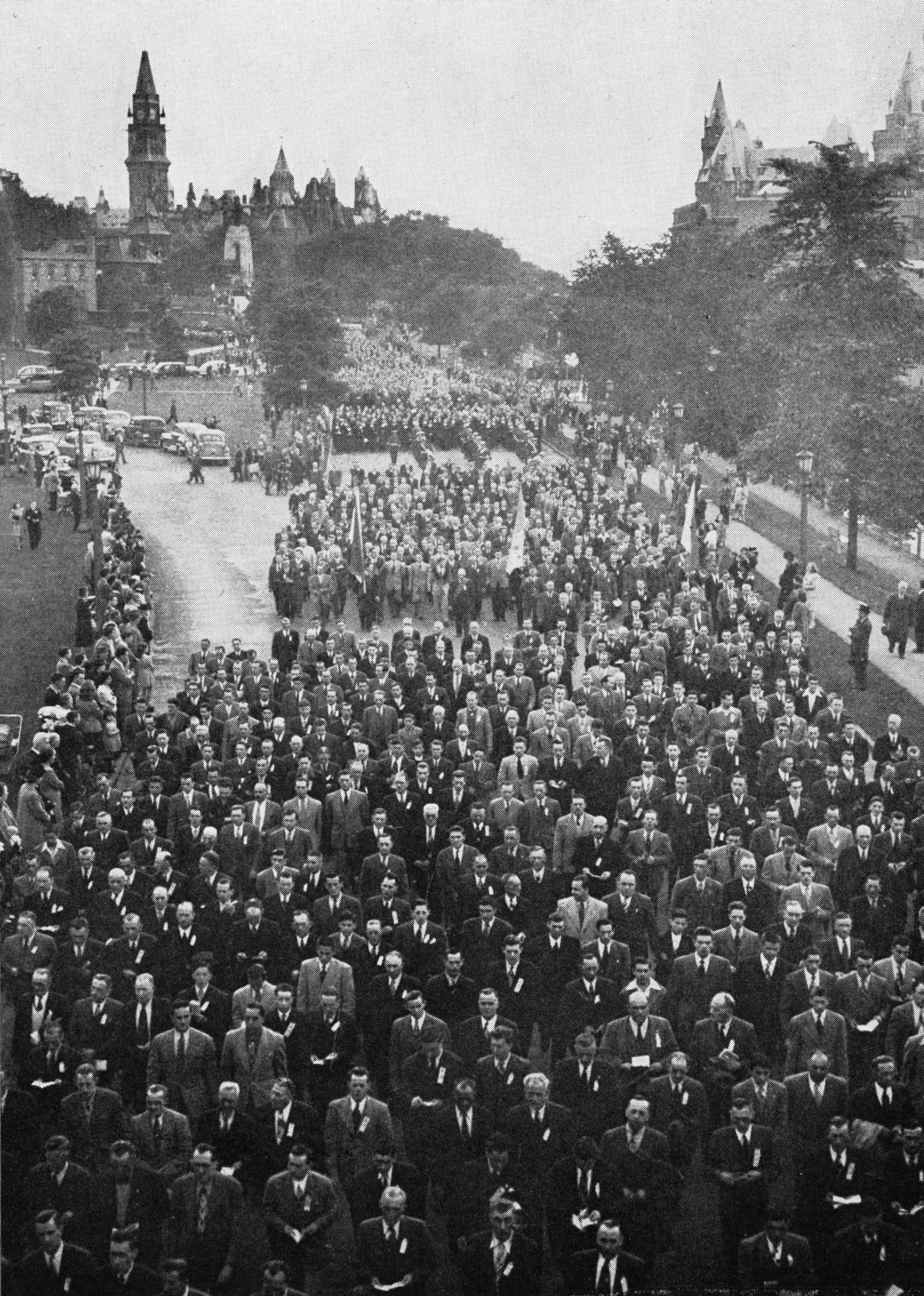 Black and white photograph of a grand procession. Men in suits and ties are walking down a roadway, some holding booklets, others holding flags. Spectators are massed along the route. In the distance  behind them, buildings of Parliament.
