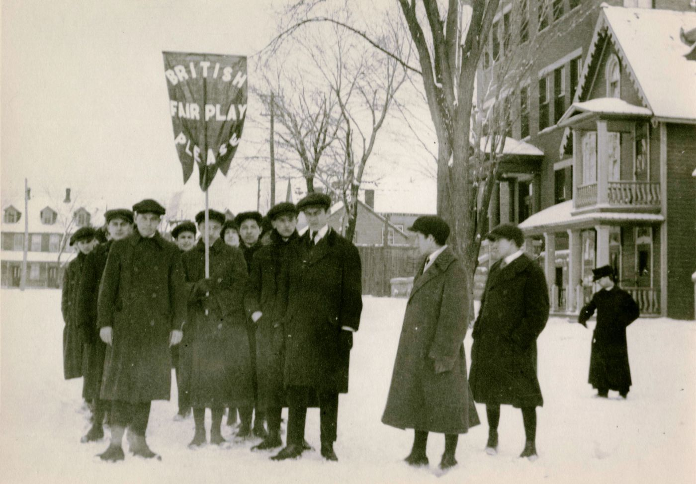 "A small group of people dressed in winter clothing stand outside, in the snow in an open space surrounded by brick buildings and trees. One of the group members holds a flag with English text reading ""BRITISH FAIR PLAY PLEASE"" in capital letters."