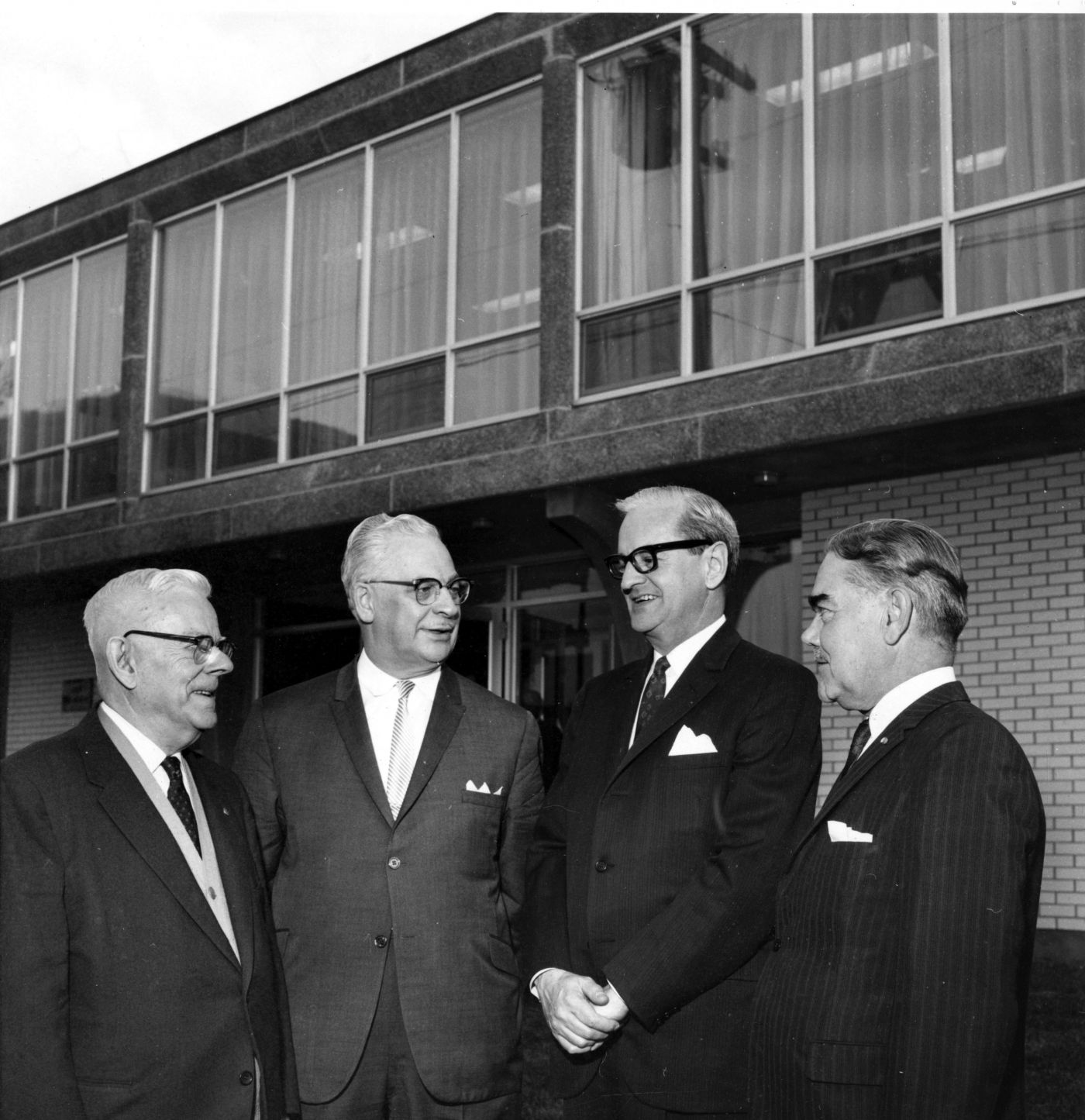 Black and white photograph of four elderly men wearing suits and ties, talking in front of a two-storey brick building. The second floor is lined with large windows.