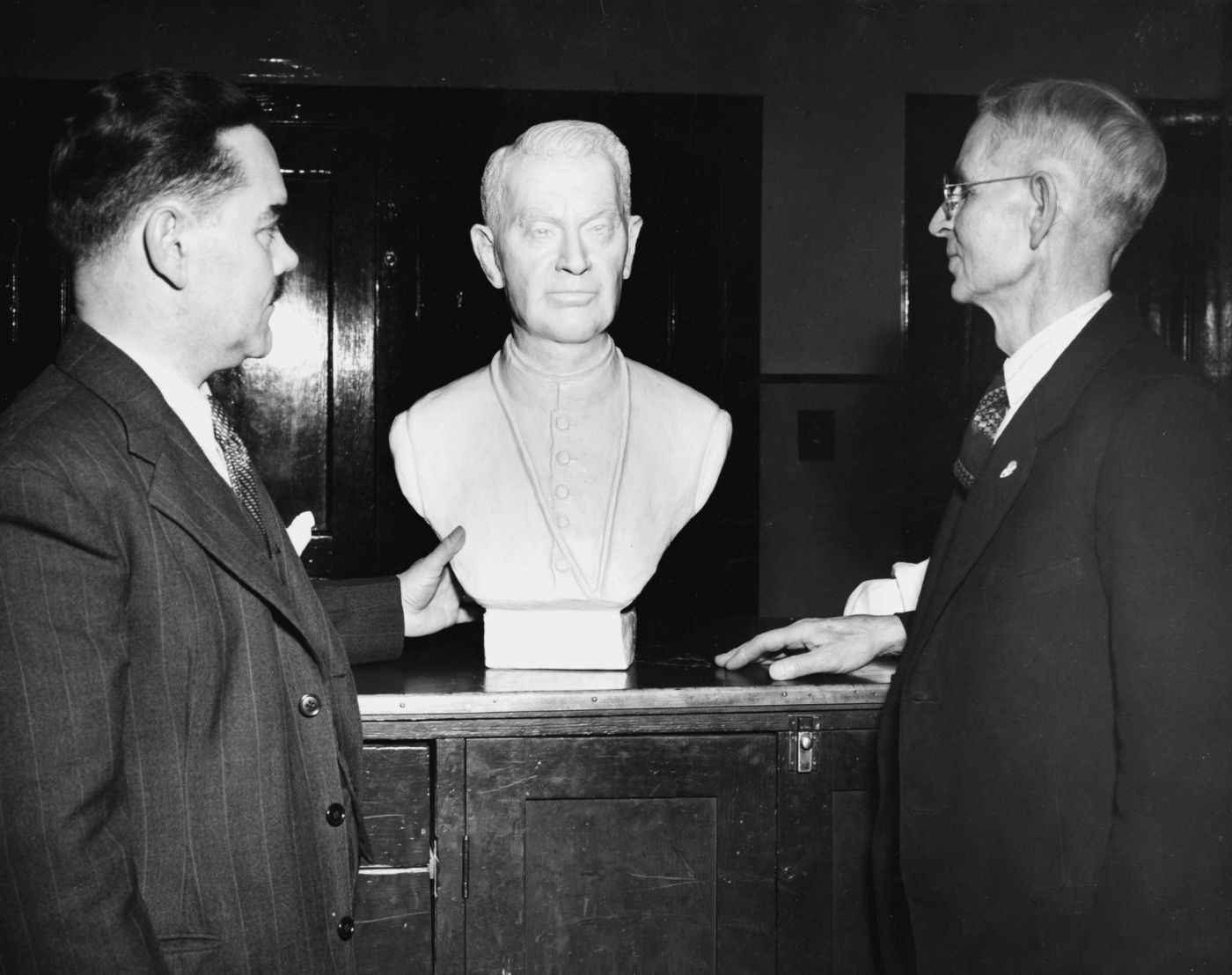 Black and white photograph of two men, in suits and ties, standing on either side of the plaster bust of a religious, middle-aged figure. The first man, middle-aged and mustached, touches the lower part of the figure with his left hand; the second, older and wearing glasses, places his right hand on the chest where the bust is placed.