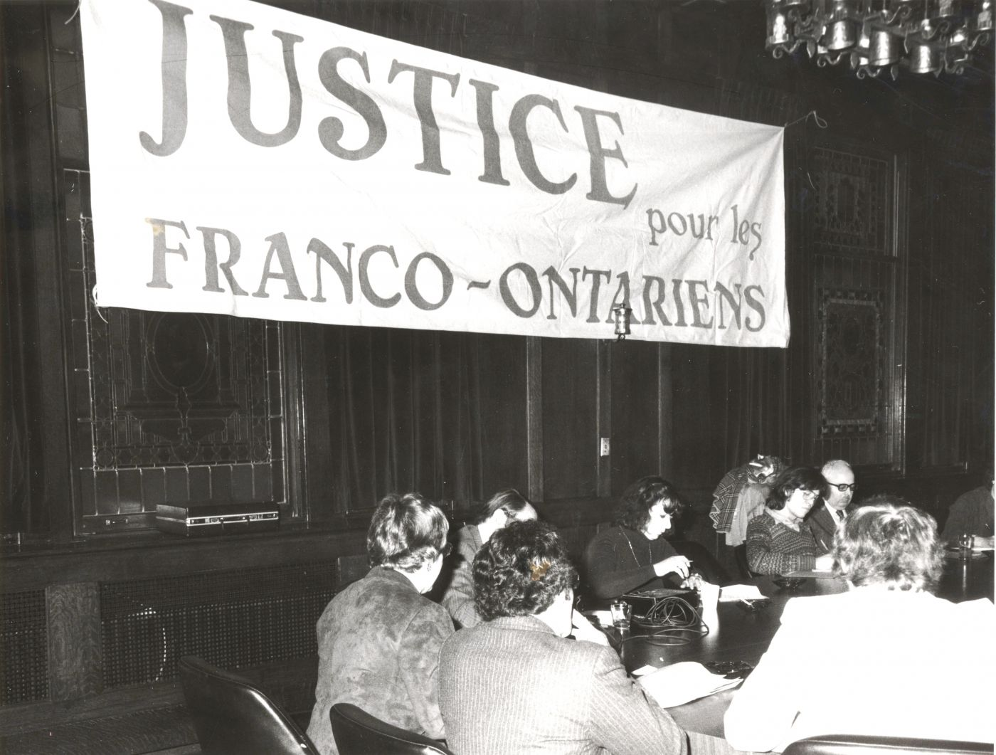 Photographie en noir et blanc d'une réunion qui se tient dans une salle aux murs sombres, masqués par une bannière où est inscrit : « JUSTICE pour les FRANCO-ONTARIENS ». Apparaissent, de dos, une dizaine d'hommes et des femmes, assis à une table de conférence.