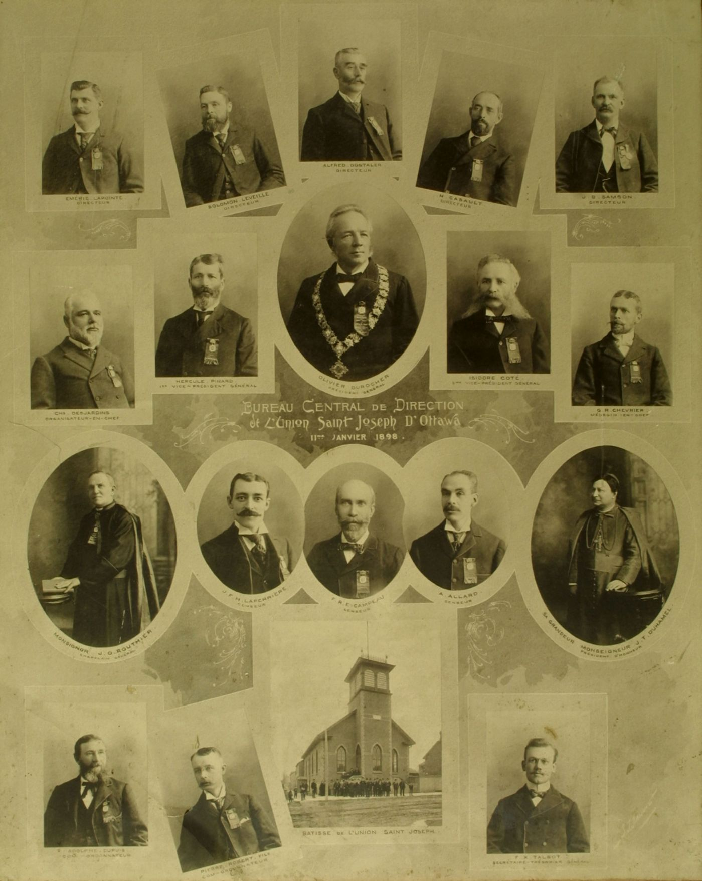 Display board with 18 black and white photographs, depicting men in suits and ties, with the exception of two clerics. Names and titles appear below the photographs. The man in the middle picture wears  the Mayor's chain of office. A picture of a two-storey building with large front tower is included, as well as a caption in French.