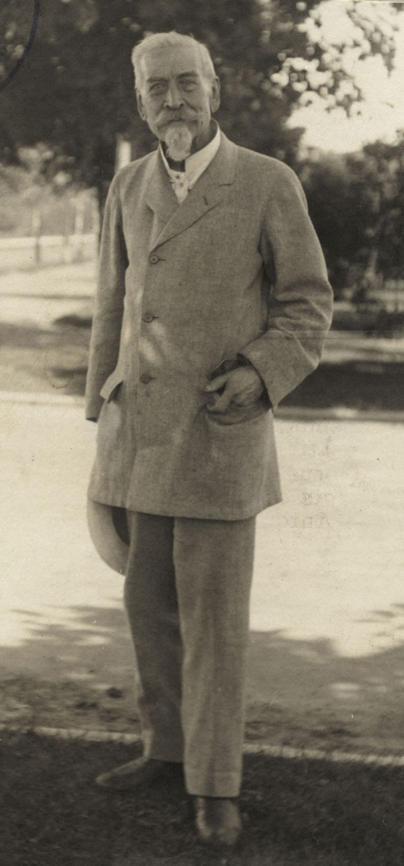 Sepia photograph of an elderly man with white hair, mustache and beard, dressed in a pale suit. He stands at the edge of a tree-lined street, one hand in a pocket, the other holding a hat.