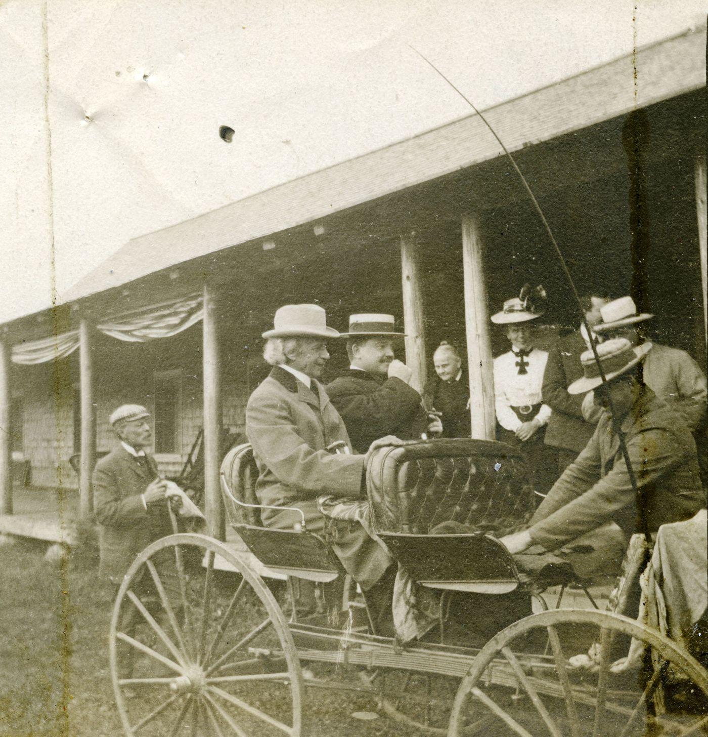 Photographie en noir et blanc de deux hommes bien mis, assis dans un boghei devant un bâtiment en bois. Les cheveux blancs du premier sont visibles malgré son chapeau. Le second, plus jeune, porte la moustache.  Un troisième homme prépare le boghei. Quelques personnes les observent.