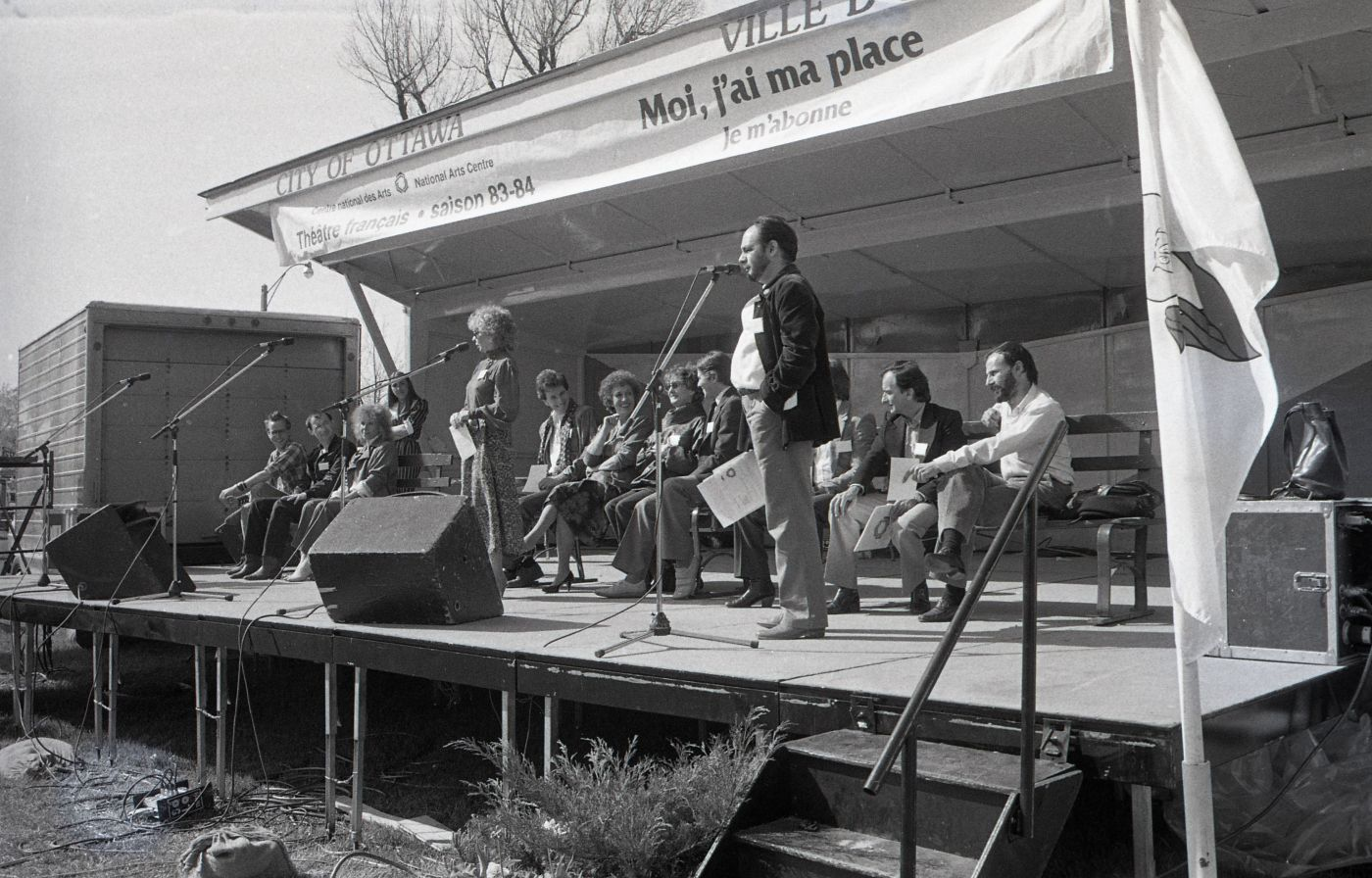 Photographie en noir et blanc d'un homme et d'une femme d'âge moyen parlant au microphone sur une scène extérieure. Derrière eux, une dizaine de personnes assises sur des bancs. Une bannière au-dessus de la scène sur laquelle est écrit : « Centre national des Arts  -  National Arts Centre ; Théâtre français saison 83-84 ; Moi,  j'ai ma place ; Je m'abonne ».