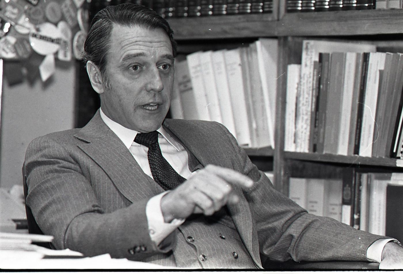 Black and white photograph, three-quarter view, of a dark-haired, middle-aged man wearing a grey pin-striped suit, white shirt and dark tie. He is speaking, pointing with his index finger. Behind him, a bookshelf and part of a bulletin board.