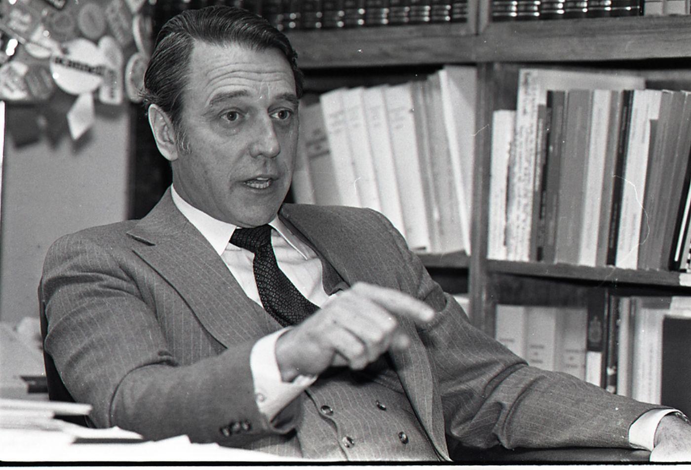 Photographie en noir et blanc d'un homme d'âge moyen, en complet et cravate. L'homme est assis devant les rayons d'une bibliothèque. Sa bouche est entrouverte et il pointe l'index de sa droite vers l'objectif.