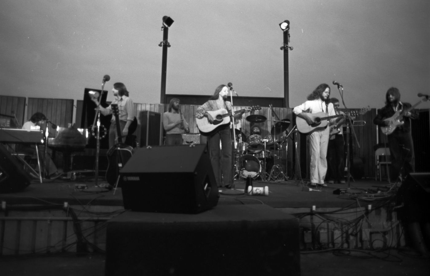"""Black and white photograph of seven musicians (three guitarists, a bassist, a pianist, and two percussionists) on an outdoor stage in dim light. The group includes six long-haired men and a woman, of mature age, wearing casual clothes.  """