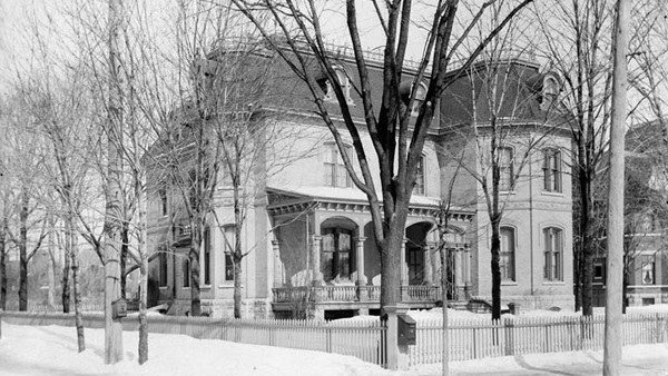 Black and white photograph of a three-story house with a front porch. The house, seen in winter, is set in a large yard surrounded by a fence. The yard and street are lined with trees.