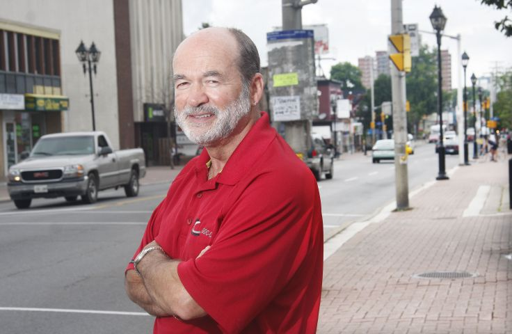 Colour photograph of a middle-aged man dressed in a red polo shirt, arms crossed, with a busy downtown street in the background. He displays an air of determination.