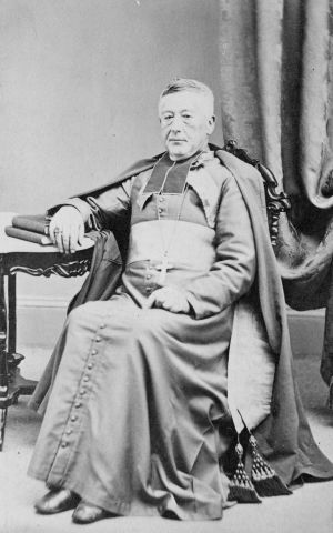 Black and white photograph of an elderly man wearing the liturgical garments of a bishop. He does not wear the cap. He sits on a chair, his right arm resting on a table, his hand resting on books. He wears a serious expression.