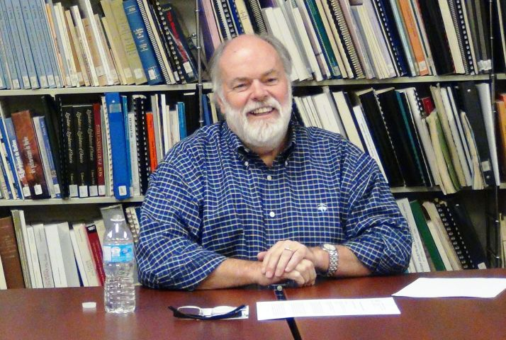 Color photograph of a bearded, middle-aged man sitting at a table in front of a bookshelf. He is dressed in a chequered shirt and smiles at the camera.