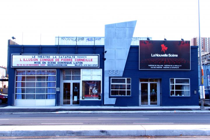 "Colour photograph of a one-story brick theatre building, painted dark blue, with several glass doors and windows. A marquee announces that the next play will be ""L'Illusion comique de Corneille,"" presented by the Théâtre la Catapulte."