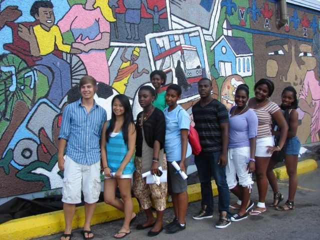 Colour photograph of a group of teenagers from different racial groups standing in front of a coloured mural representing the multicultural and inclusive character of the place.