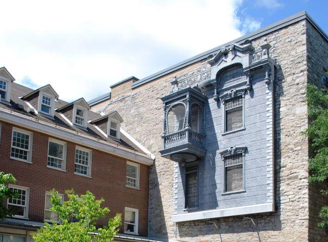 Photographie en couleur d'une cour intérieure avec, à l'avant-plan, une fontaine. Derrière, deux bâtiments, un en bois et l'autre en pierre. La façade en métal d'une maison est accrochée en haut d'un mur du bâtiment de pierre.
